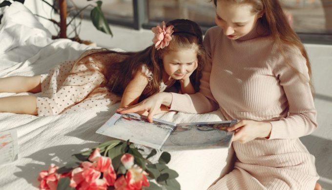 cheerful-mother-and-daughter-reading-book-on-bed-3875332